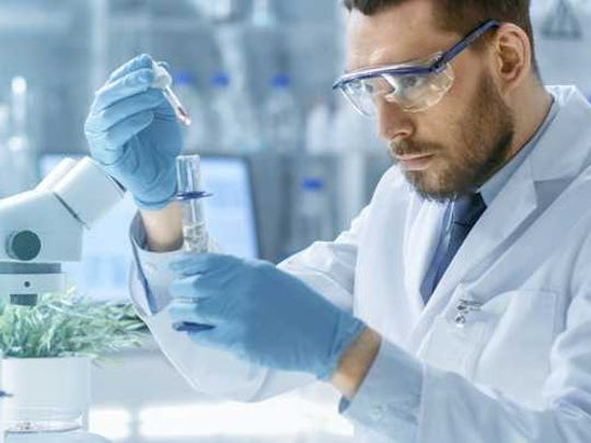 Man in lab attire holding a dropper over a test tube.