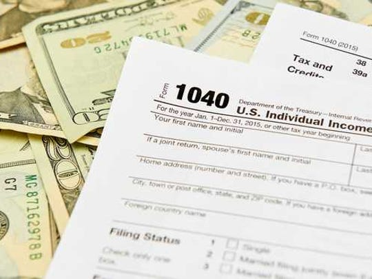 Tax form 1040 on top of a pile of twenty dollar bills.