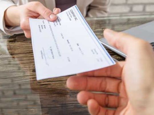 A person hands over a check.