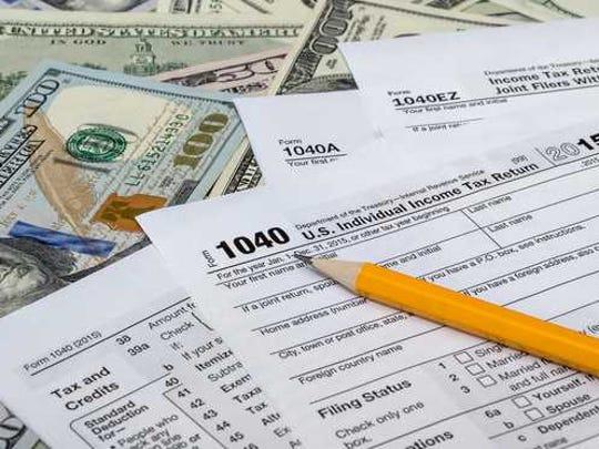 Tax forms lay atop hundred dollar bills.