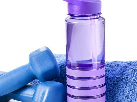 A reusable plastic water bottle next to dumbbells and