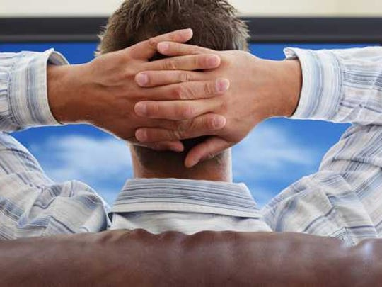 Man watching tv with hands rested behind his head.