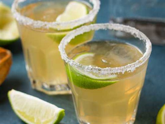 Two margaritas on the rocks with lime.