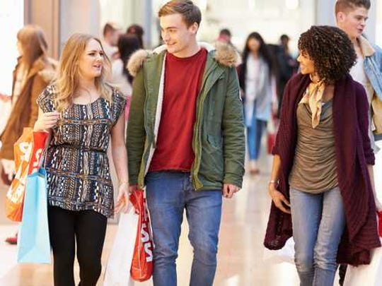 Three young friends shopping in a mall.