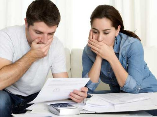Couple looking at bills with hands over their mouths.
