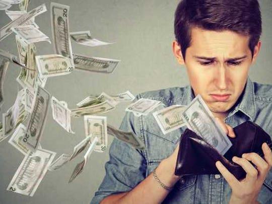 A man looks in his wallet as money flies away.