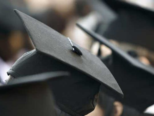 A row of graduation caps on wearers that are not visible.