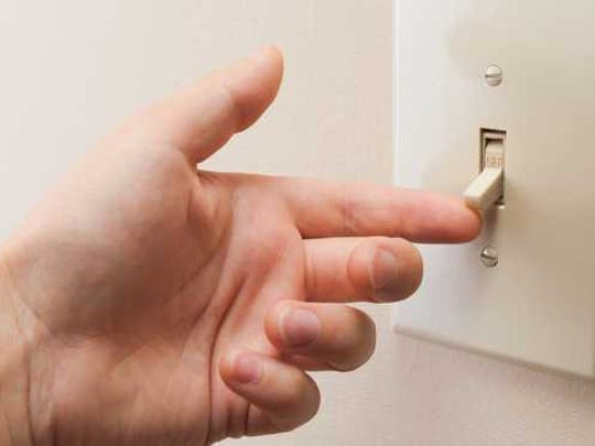 Finger flipping a light switch.