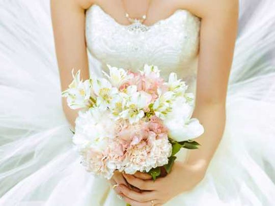 Woman kneels in wedding dress holding bouquet.