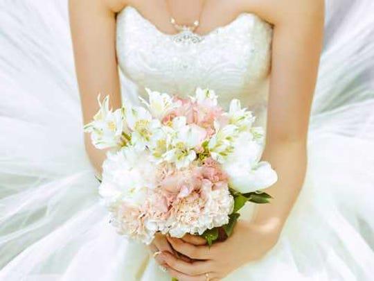 Woman kneels in wedding dress holding bouquet.