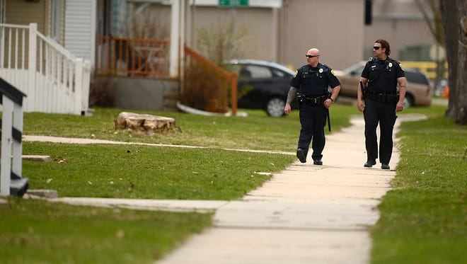Green Bay Police officers John LaValley, left, and Luke Lansbach walk along South Chestnut Avenue in Green Bay during a patrol in April. Police are working with residents to improve safety in the neighborhood between the Fox River and railroad tracks.