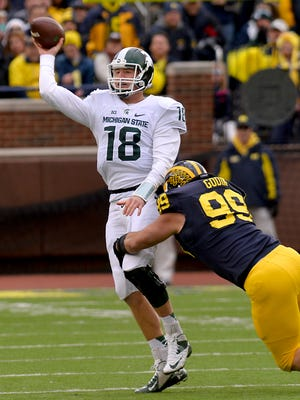 MSU quarterback Connor Cook gets off a pass for a completion as Michigan's  Matthew Godin closes in too late Saturday in Ann Arbor.