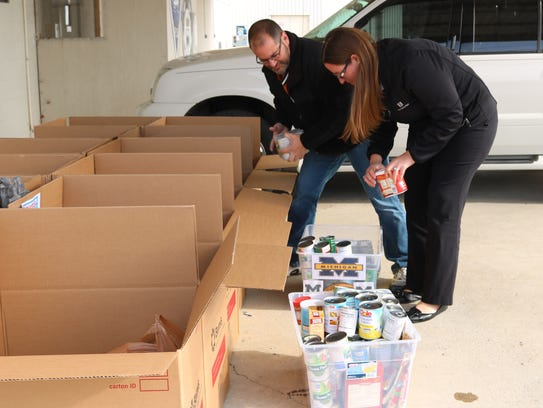Robert and Brittany Christiansen unload boxes of donated