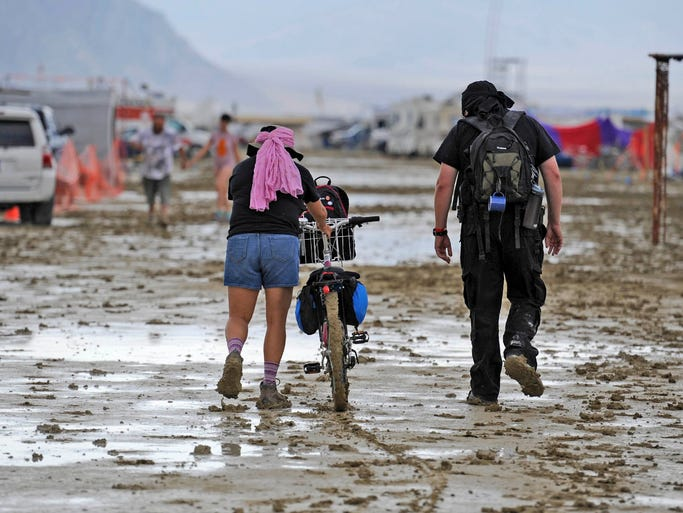 Burning Man participants walk through the muddy streets after a morning rain storm in Gerlach, Nevada  August 25, 2014.