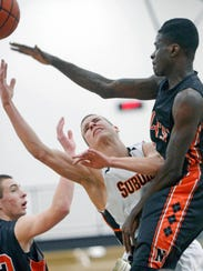 Northeastern's Braheem Riley, right, meets York Suburban's Evan Eberhardinger at the basket Saturday night during the Bobcats' 59-56 YAIAA boys' tournament quarterfinal win. (Daily Record/Sunday News -- Kate Penn)
