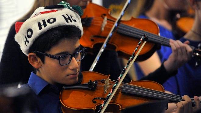 Seventh-grader Nicholas Vega plays violin during the CORE - Craig Middle School Orchestra performance Tuesday at the Center for Contemporary Arts. The show was a part of City Sidewalks downtown.