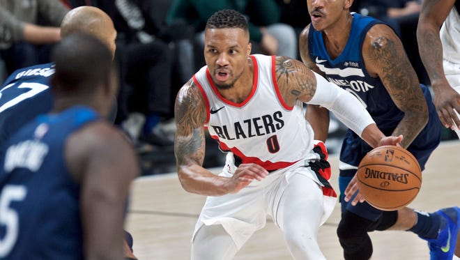 Portland Trail Blazers guard Damian Lillard dribbles as the Minnesota Timberwolves including  guard Jeff Teague, right, watch during the second half of an NBA basketball game in Portland, Ore., Wednesday, Jan. 24, 2018.