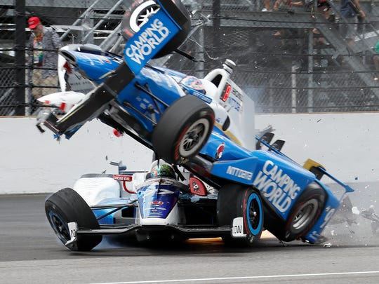 Chip Ganassi Racing IndyCar driver Scott Dixon (9) runs over Schmidt Peterson Motorsports IndyCar driver Jay Howard (77) coming out of turn one during the 101st running of the Indianapolis 500 at Indianapolis Motor Speedway Sunday, May 28, 2017.