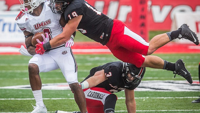 Ball State's Ben Ingle brings down University of Massachusetts' Marquis Young during their game at Scheumann Stadium Saturday, Oct. 31, 2015.