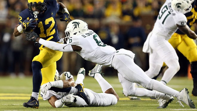 Michigan RB Chris Evans (12) breaks tackle of Michigan State S David Dowell (6) during the first quarter of a game against Michigan State at Michigan Stadium in Ann Arbor on Sat., Oct. 7, 2017.