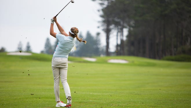 Young woman hits a perfect golf shot