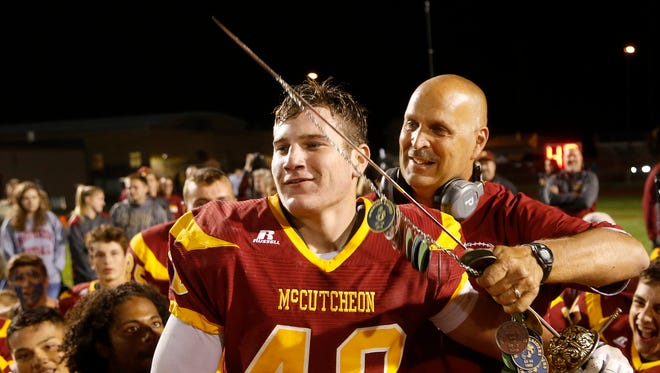 McCutcheon head coach Ken Frauhiger gives senior Walter Foster the honor of hoisting the sword after the Mavericks defeated county rival Harrison 21-7 Friday, September 29, 2017, at McCutcheon High School.