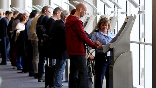 Passengers use the Automated Passport Control Kiosks set up for international travelers arriving at Miami International Airport on March 4, 2015.