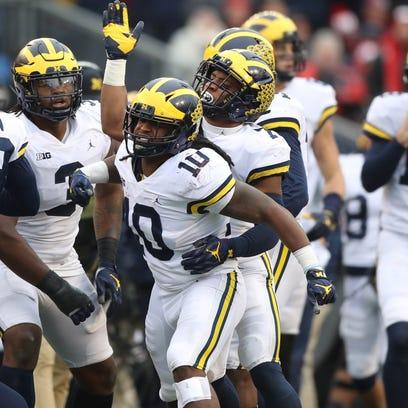 Michigan's Devin Bushcelebrates his interception of