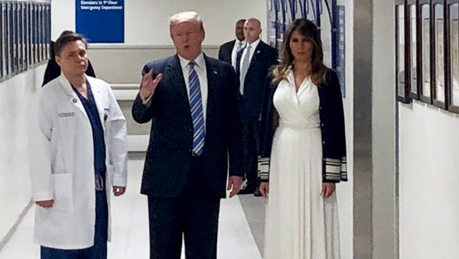 President Trump is accompanied by trauma surgeon Dr. Igor Nichiporenko and his wife Melania Trump during a visit to the victims of the Parkland school shooting, at the Broward Health North medical center in Pompano Beach, Florida.