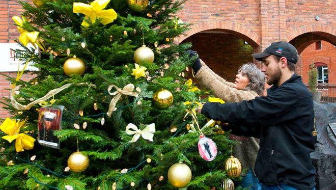 People decorate the Christmas Tree in downtown Walla Walla, Wash.