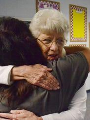 Retired teacher Bert Baldwin, right, hugs teaching
