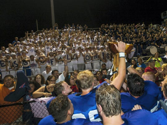 Cedar Crest football team takes the Cedar Bowl over to the student section after Cedar Crest defeated Lebanon 41-7 as they faced off in the 44th annual Cedar Bowl at Cedar Crest's Earl Boltz Stadium on Friday, September 4, 2015.