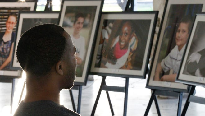 Calvin Carter listens to a speaker at a foster care event in 2013. Behind him were portraits of children waiting to be adopted.