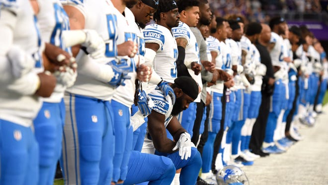 Lions linebacker Steve Longa, center, takes a knee with teammate Jalen Reeves-Maybin during the national anthem before the game against the Vikings on Sunday, Oct. 1, 2017 at U.S. Bank Stadium in Minneapolis.