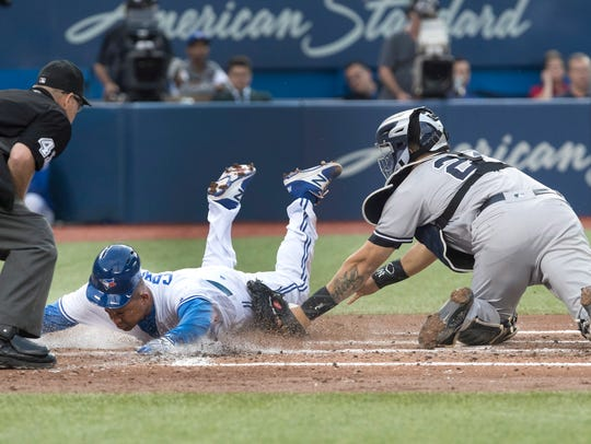 The Blue Jays' Ezequiel Carrera scores ahead of the