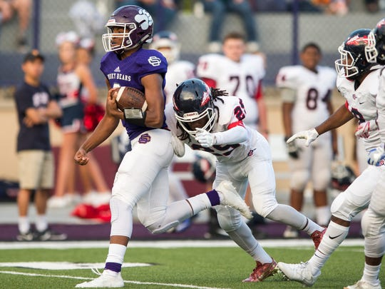Sevier County quarterback Cam Burden (2) avoids a tackle by South-Doyle defensive back Nate Adbeyo (25) during a game between South-Doyle and Sevier County on Thursday, Sept. 14, 2017.