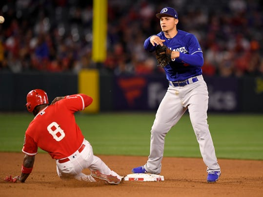 Los Angeles Angels' Justin Upton, left, is forced out at second as Los Angeles Dodgers shortstop Corey Seager throws out Kole Calhoun at first during the fourth inning of a preseason baseball game Sunday, March 25, 2018, in Anaheim, Calif. (AP Photo/Mark J. Terrill)