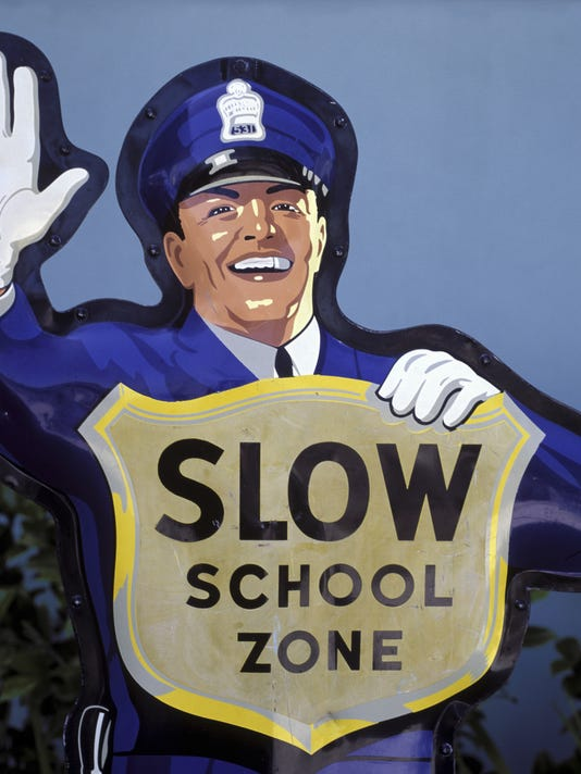 Cut out sign of an officer holding a school zone sign