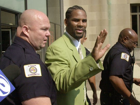 Singer R. Kelly waves to fans as he is escorted from