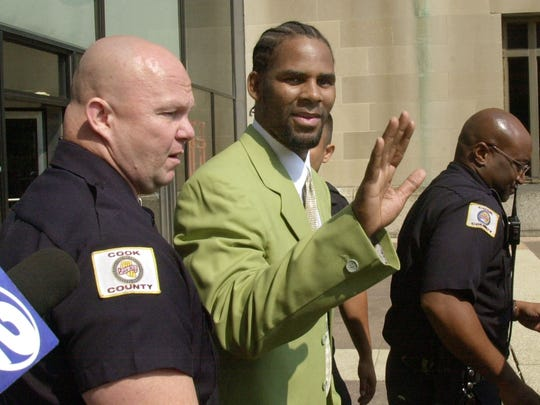 Singer R. Kelly waves to fans as he is escorted from Cook County Court in Chicago, Friday, Aug. 30, 2002.