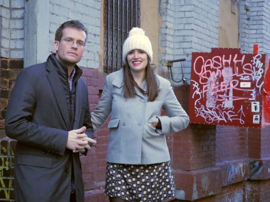 """John Green and Sarah Urist Green pose outside the New York City studio of artist David Brooks during an episode of """"The Art Assignment"""" online video series."""