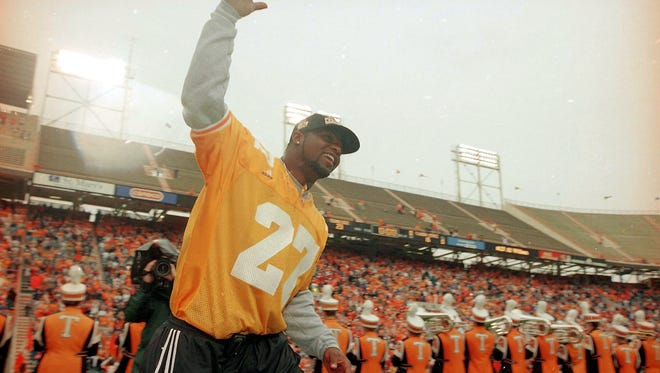 "Former Tennessee linebacker Al Wilson waves to the crowd as he runs through the ""T"" at Neyland Stadium on Jan. 30, 1999, during a celebration of the program's national championship."