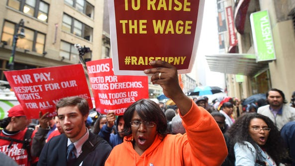 Fast-food workers hold placards in support to an increase