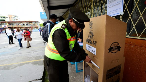 A police officer casts his vote at a polling station