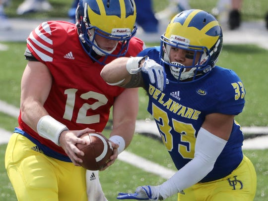 Delaware quarterback Pat Kehoe fakes a handoff to running back DeJoun Lee during Delaware's Blue-White Spring game at Delaware Stadium.