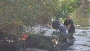 Emergency responders work on a car that submerged in a Bonita Springs canal after a crash on Monday.