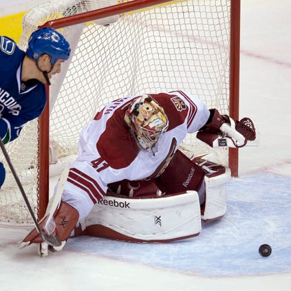 Vancouver Canucks center Shawn Matthias  tries to get a shot past Arizona Coyotes goalie Mike Smith during the first period on Monday, Sept. 29, 2014.