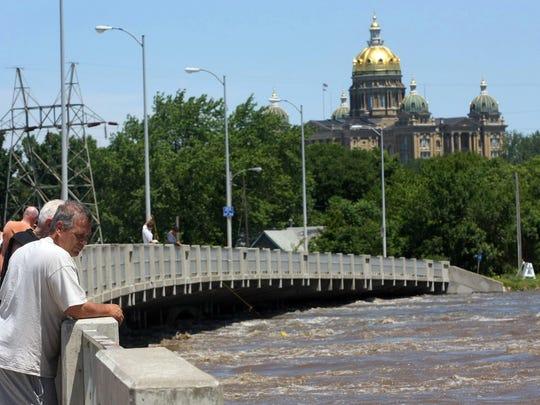People gather on the Scott Avenue bridge as water on
