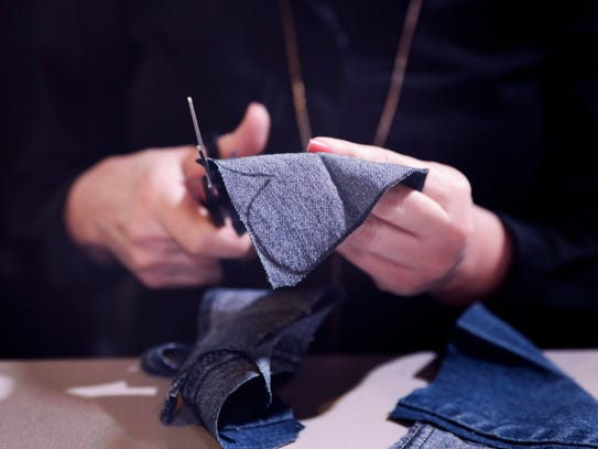 A volunteer cuts denim into patterns during a shoe