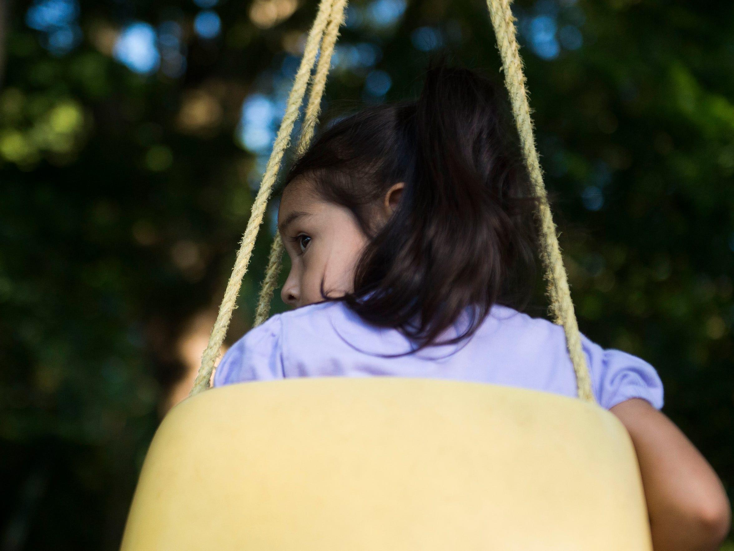 Jeylani Librado, 3, swings in her backyard in White